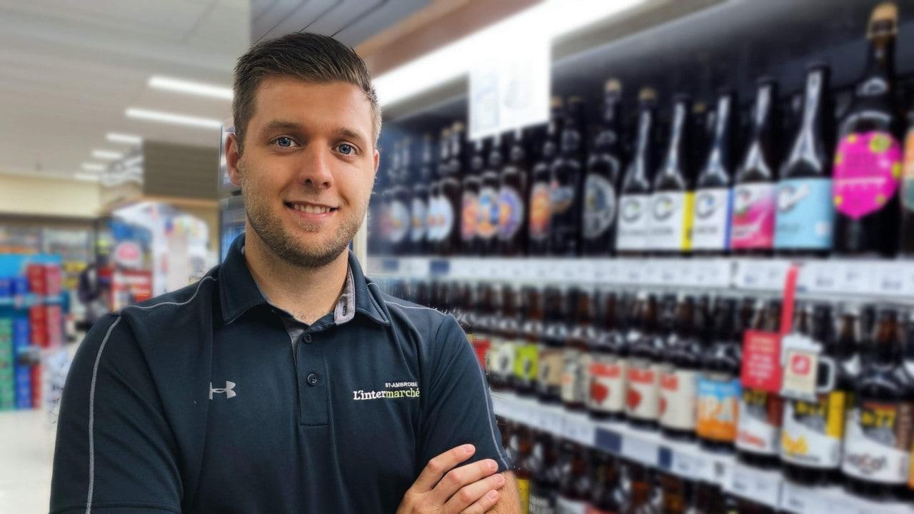 Freshmart employee leaning on shelves smiling.
