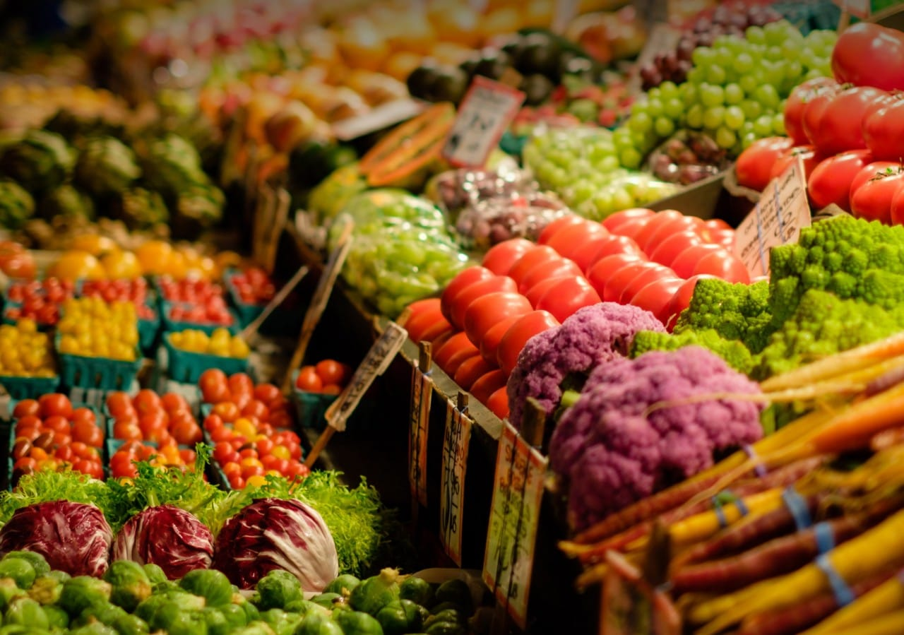 Rows of fresh vegetables in a grocery store.