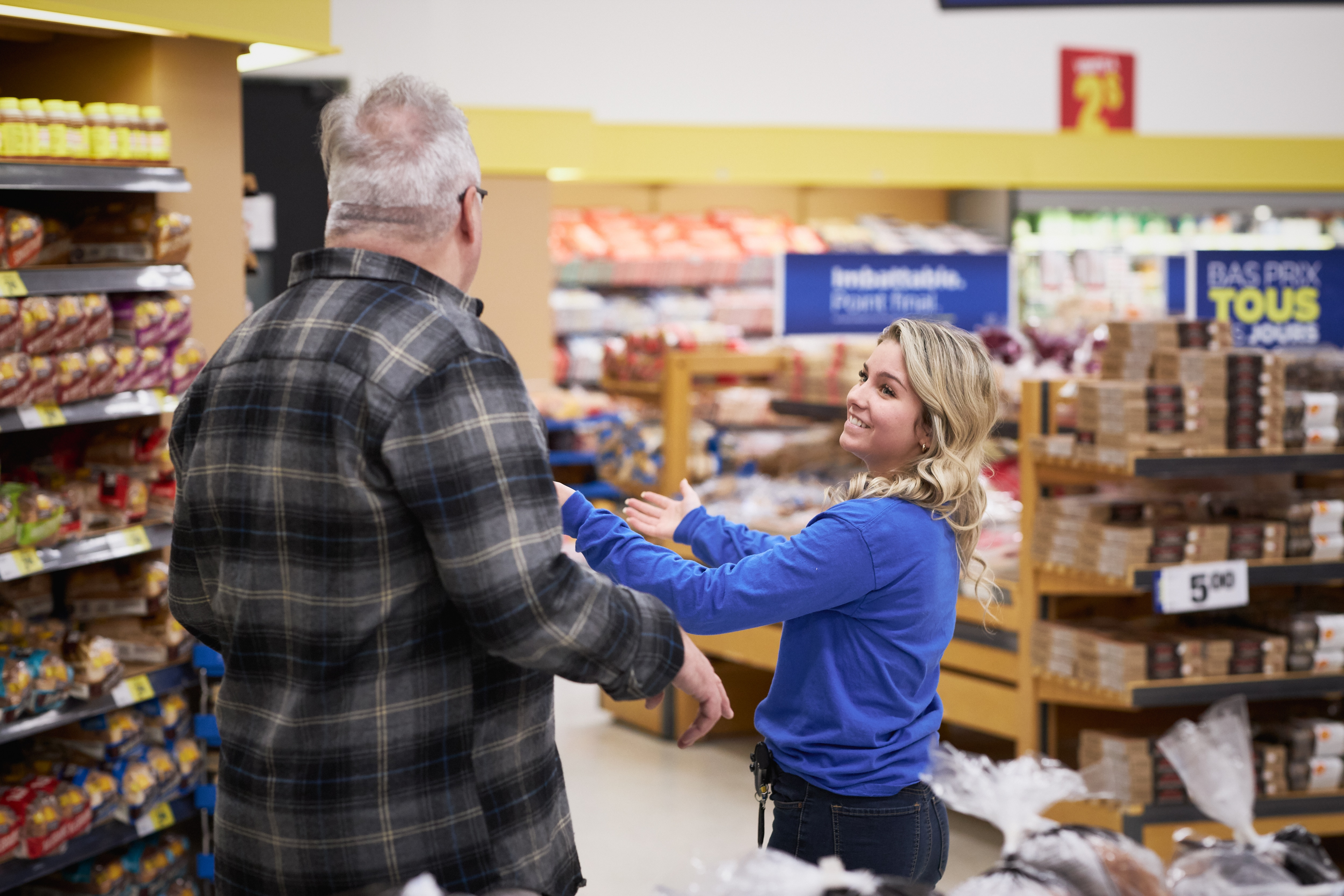 Young grocery store employee helping man in the bread section.