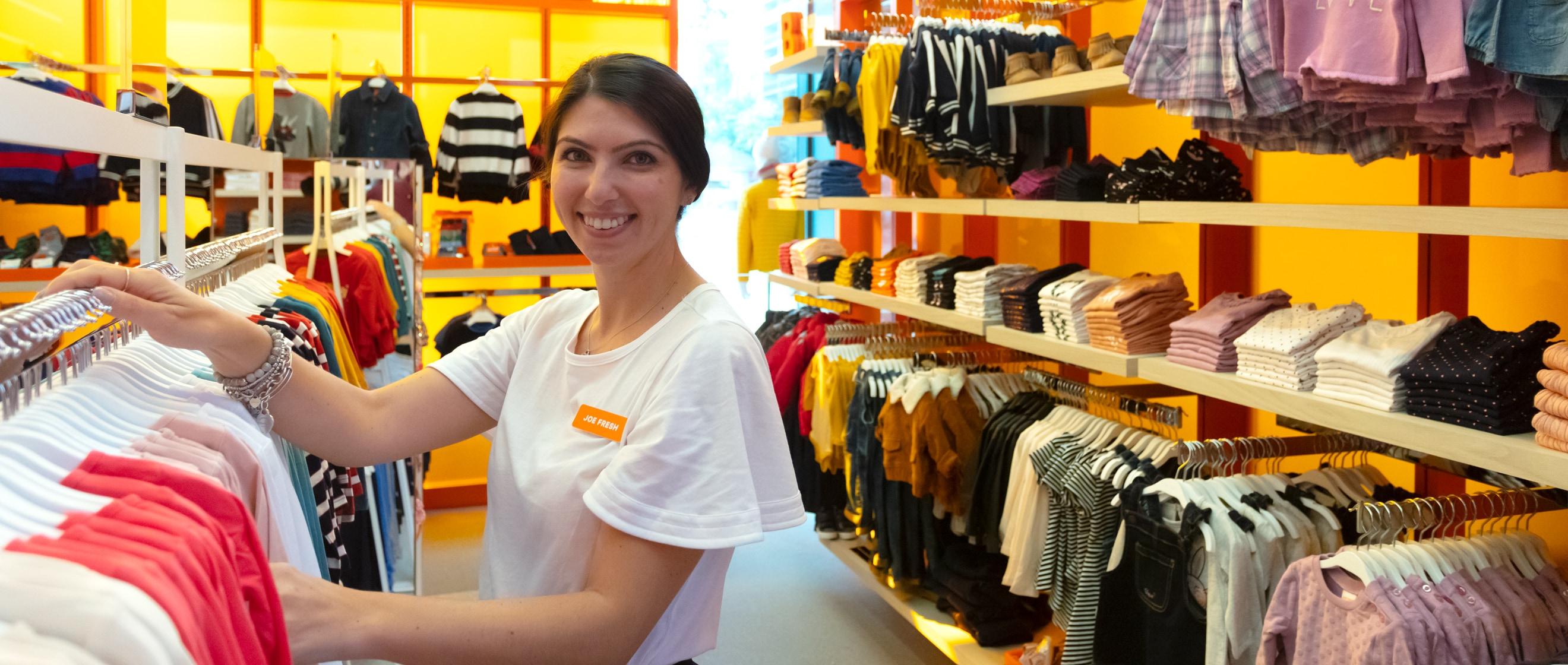 Joe Fresh employee smiling and working sorting clothes.