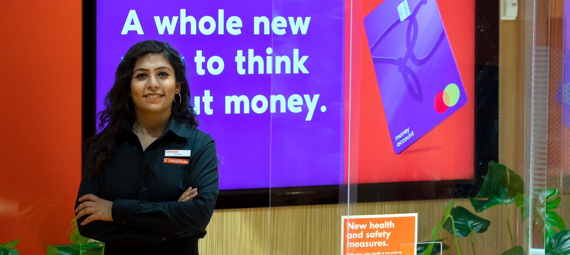PC Financial employee standing with her arms across in front of a PC Financial ad on a screen.