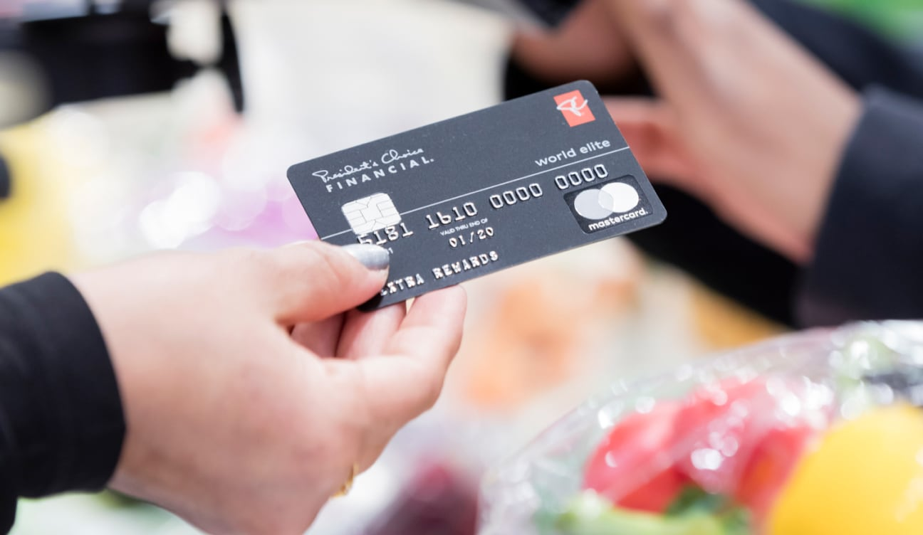 Person holding a PC World Elite credit card.