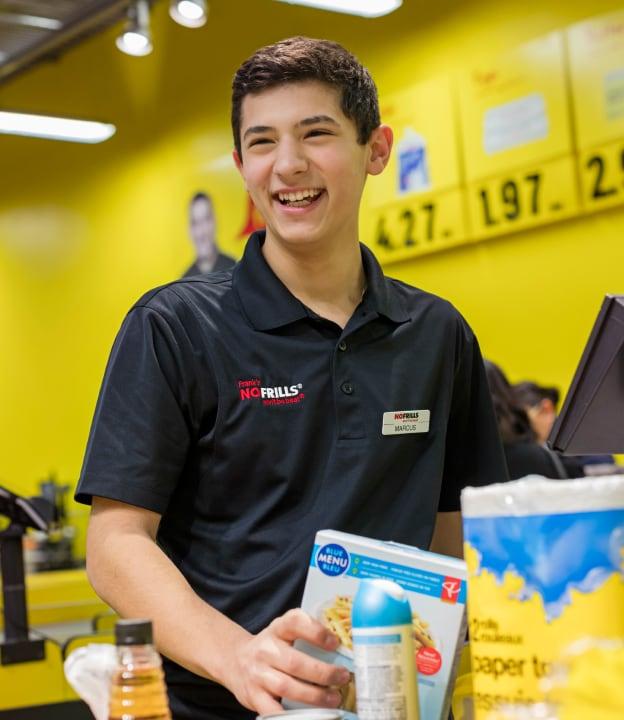 Jeune homme qui emballe son épicerie chez No Frills.