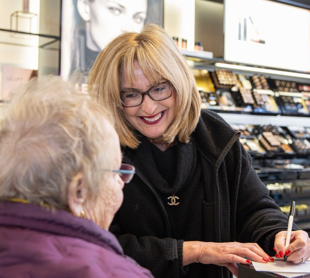 Woman working in Shoppers Drug Mart helping an elderly lady.