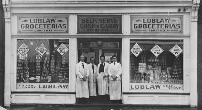 4 men in white coats standing in front of the first Loblaw Groceteria store.