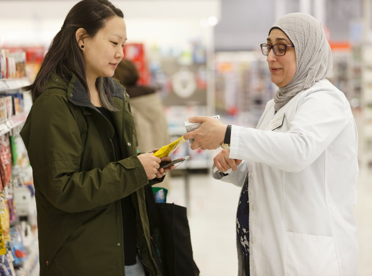 A pharmacist assisting a customer in Shoppers Drug Mart.