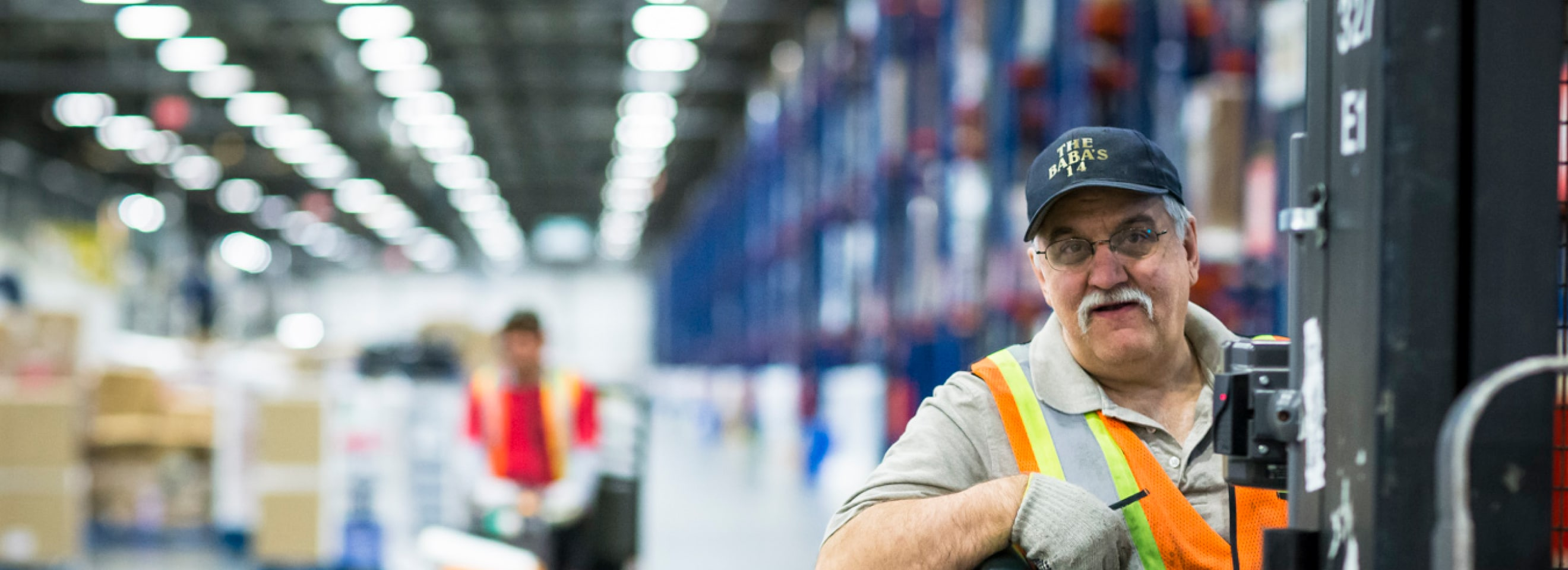 Employee with safety vest working in a warehouse.