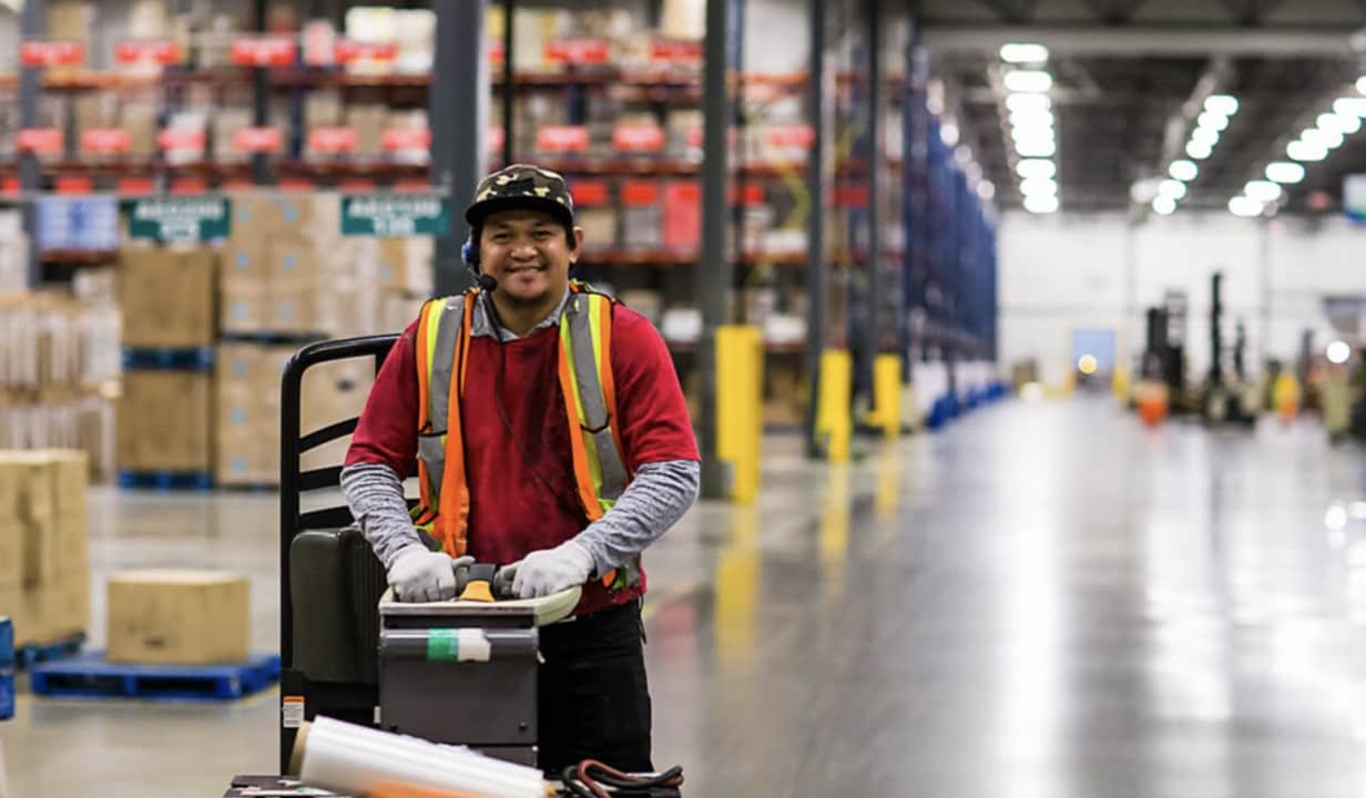 Man smiling pushing a machine in a warehouse.