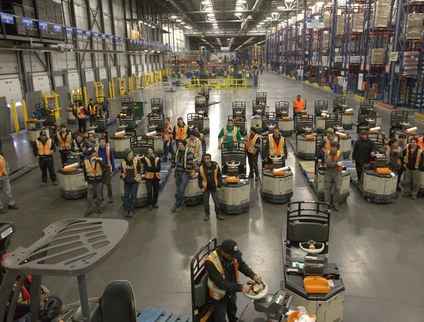 Big group of employees posing for a picture in a large warehouse.