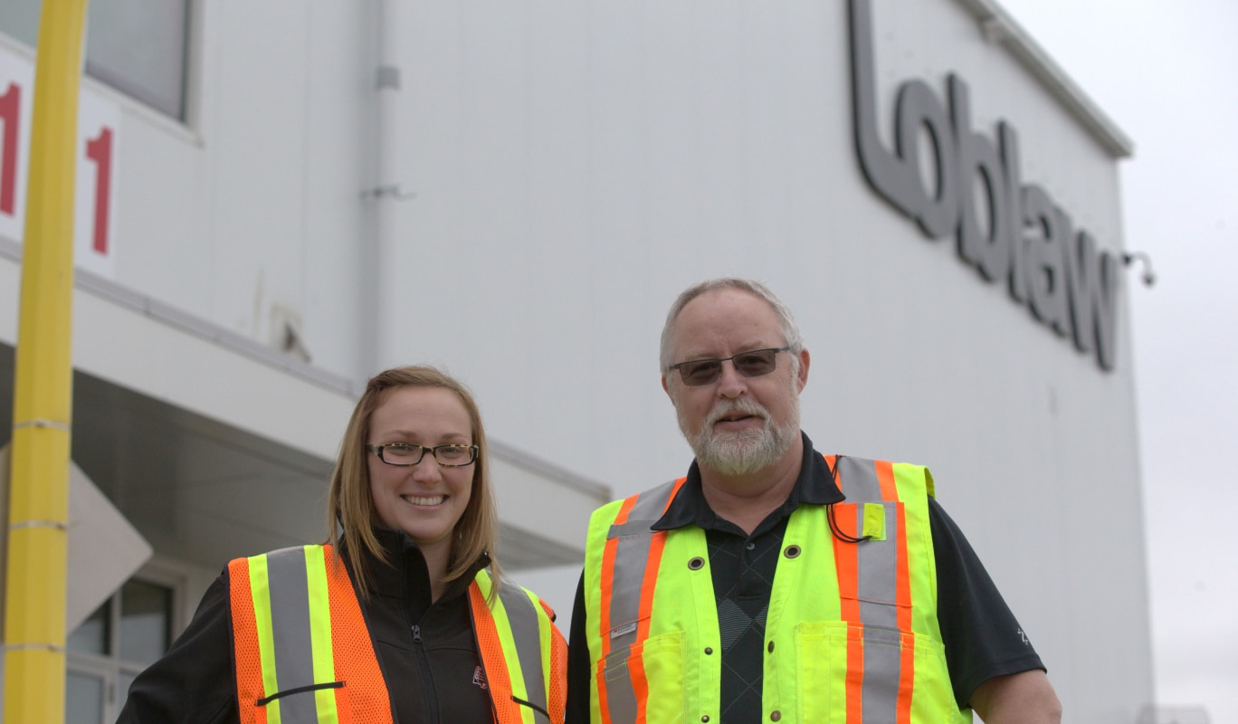 2 employees wearing bright safety vests smiling outside a building.