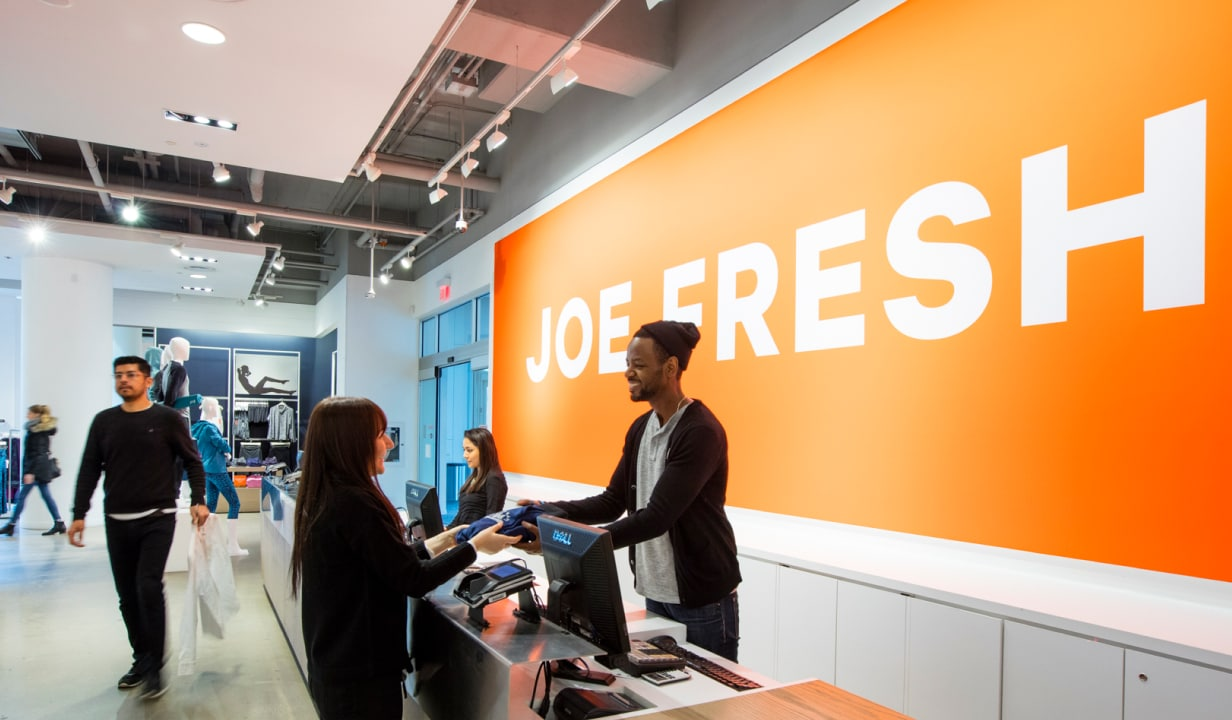 Cashier helping customer in Joe Fresh store at check out.