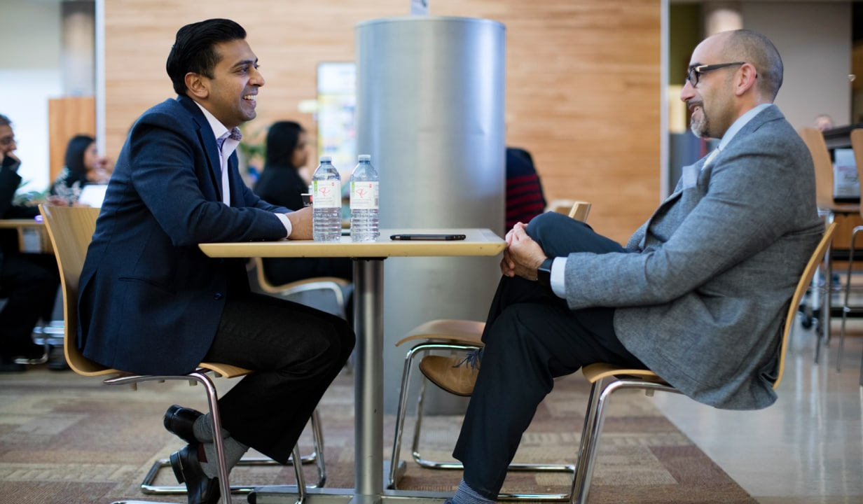 Two men in suits sitting at a table talking.