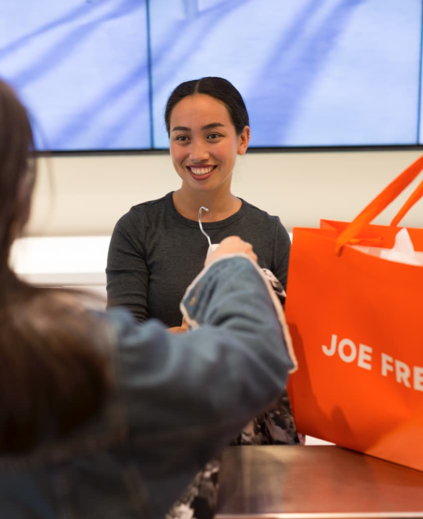 Smiling Joe Fresh employee helping a customer check out behind cash register.