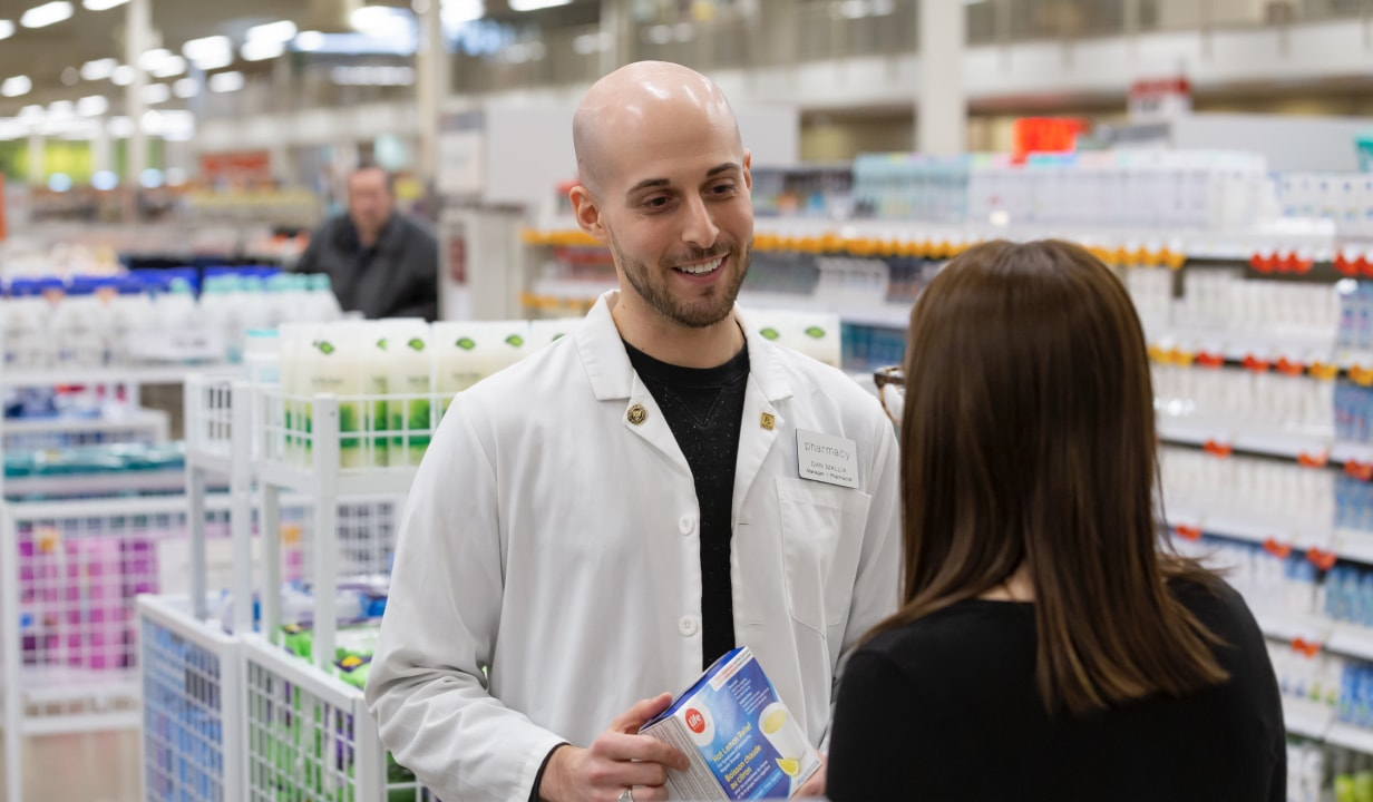 Man in white coat helping customer at Shoppers Drug Mart.