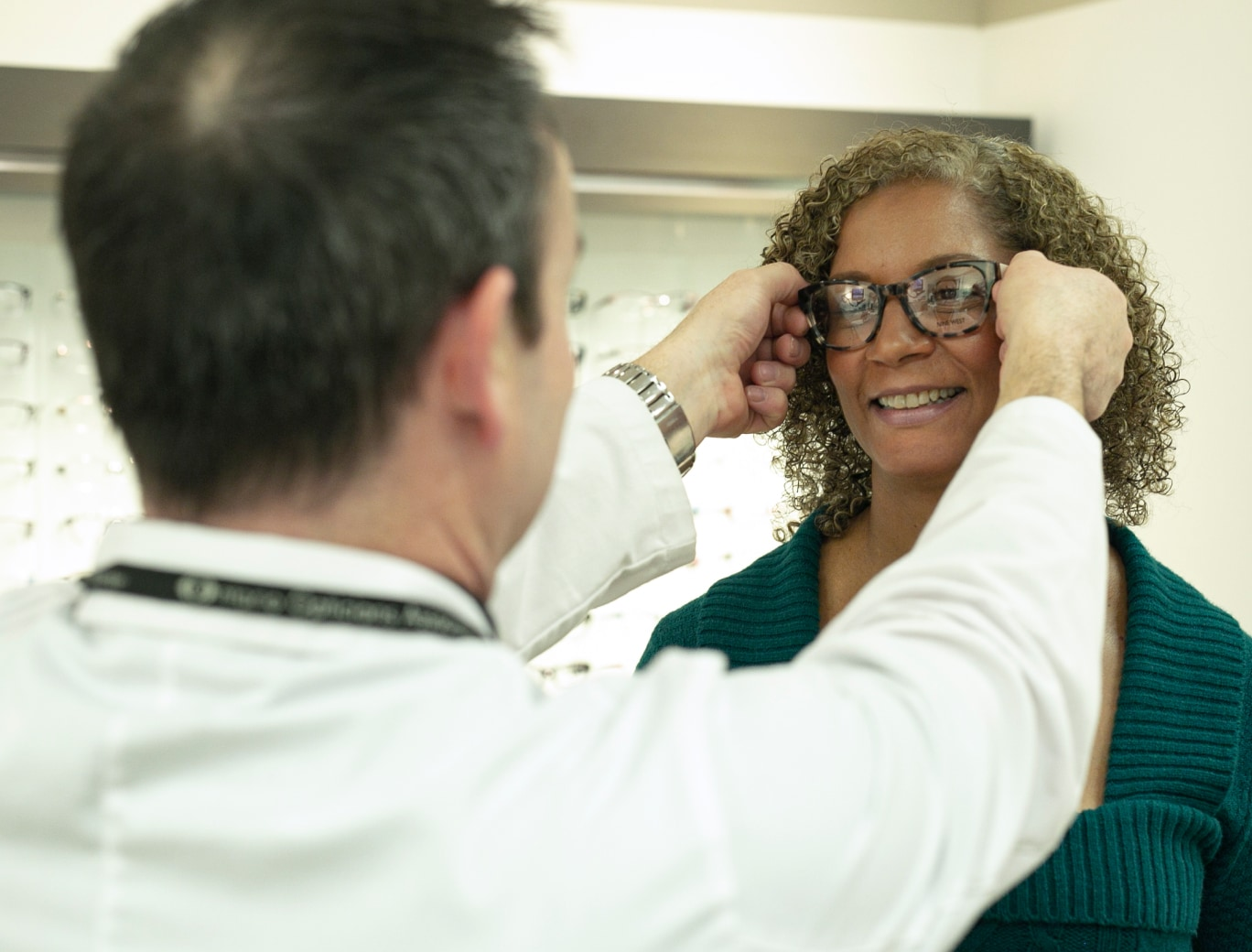 Optical employee in white coat helping fit woman with glasses.