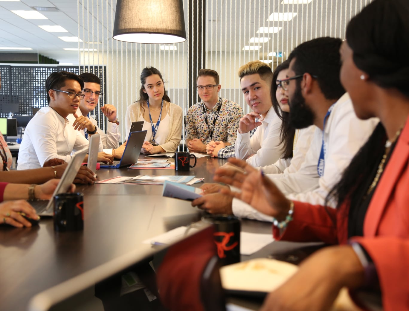 Group of interns sitting at a table with laptops listening to someone speak.