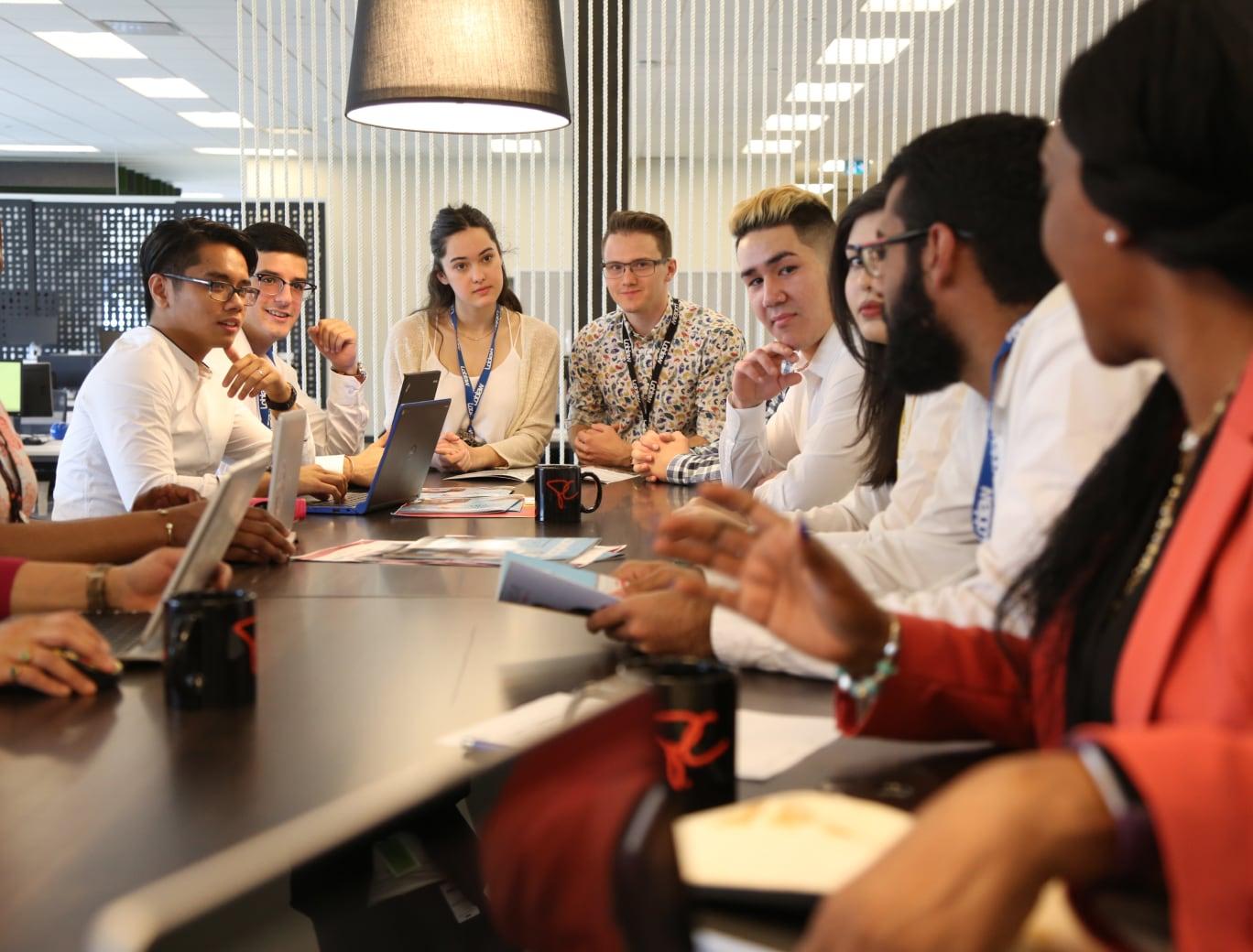 Groupe de stagiaires assis à une table avec des ordinateurs portables et écoutant quelqu'un parler.
