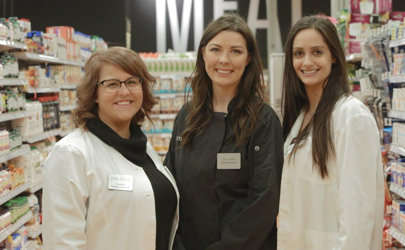 Trois collègues du secteur de la santé souriant avec des blouses blanches.