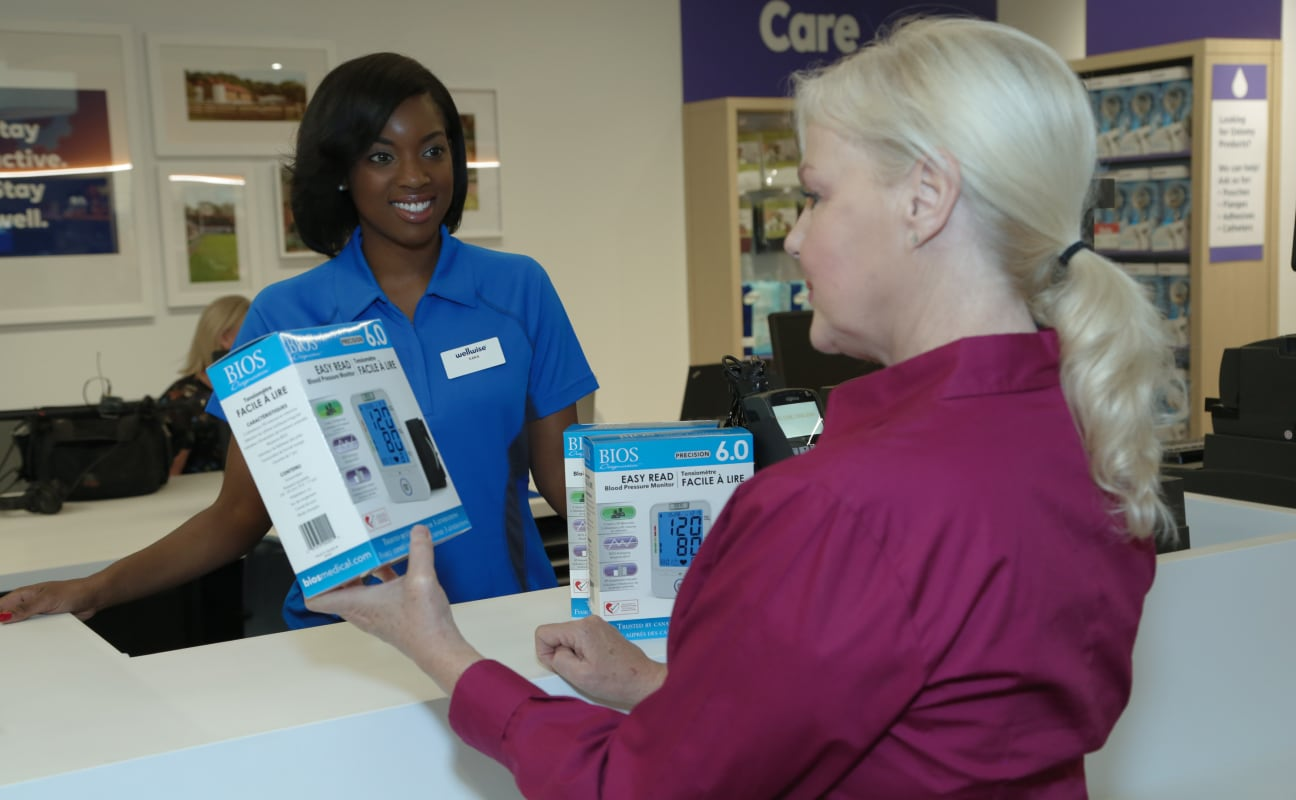Smiling healthcare worker behind a desk helping a customer with products.