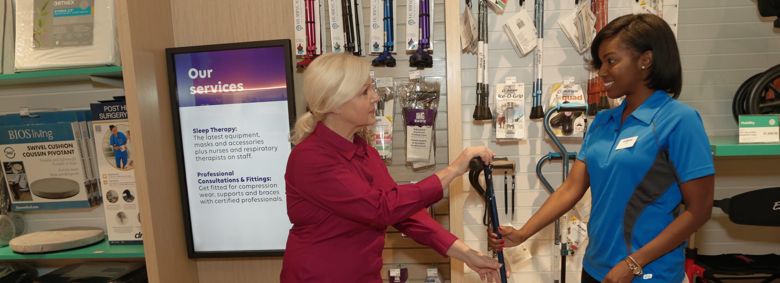 Un collègue du secteur de la santé aide une femme âgée avec des cannes.