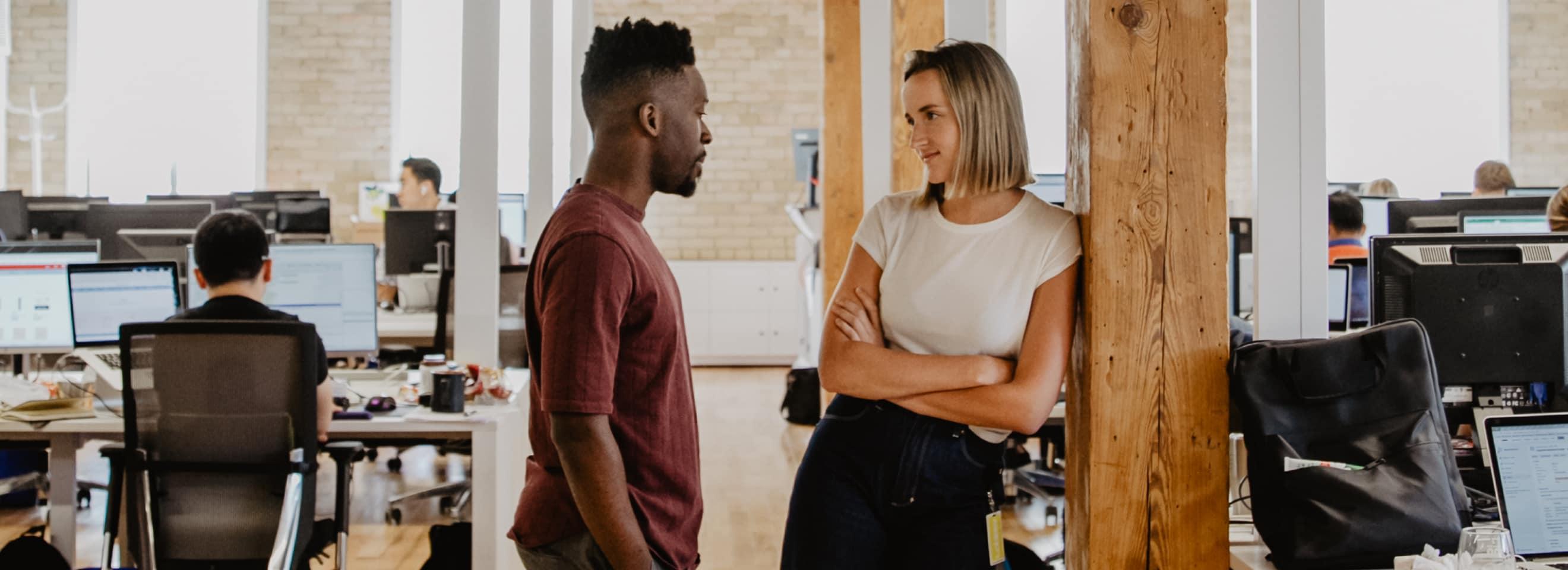 Two Loblaw employees talking in an open office space.