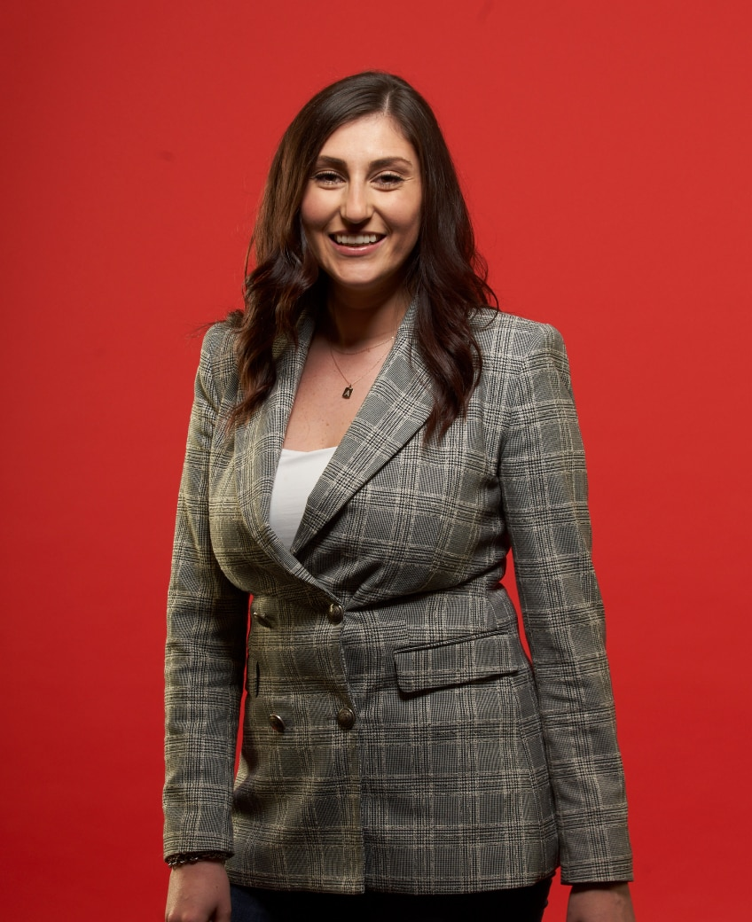 Woman in a checkered blazer smiling against a red background.