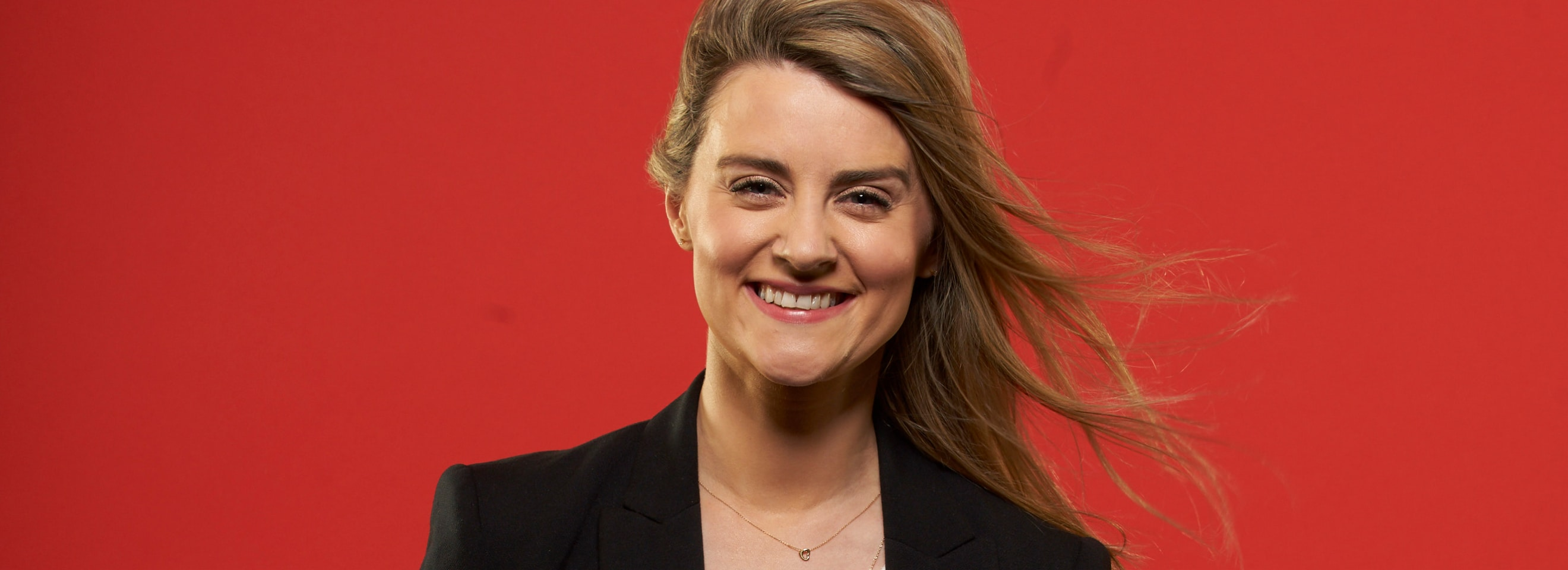 Woman in black blazer smiling on a red background.