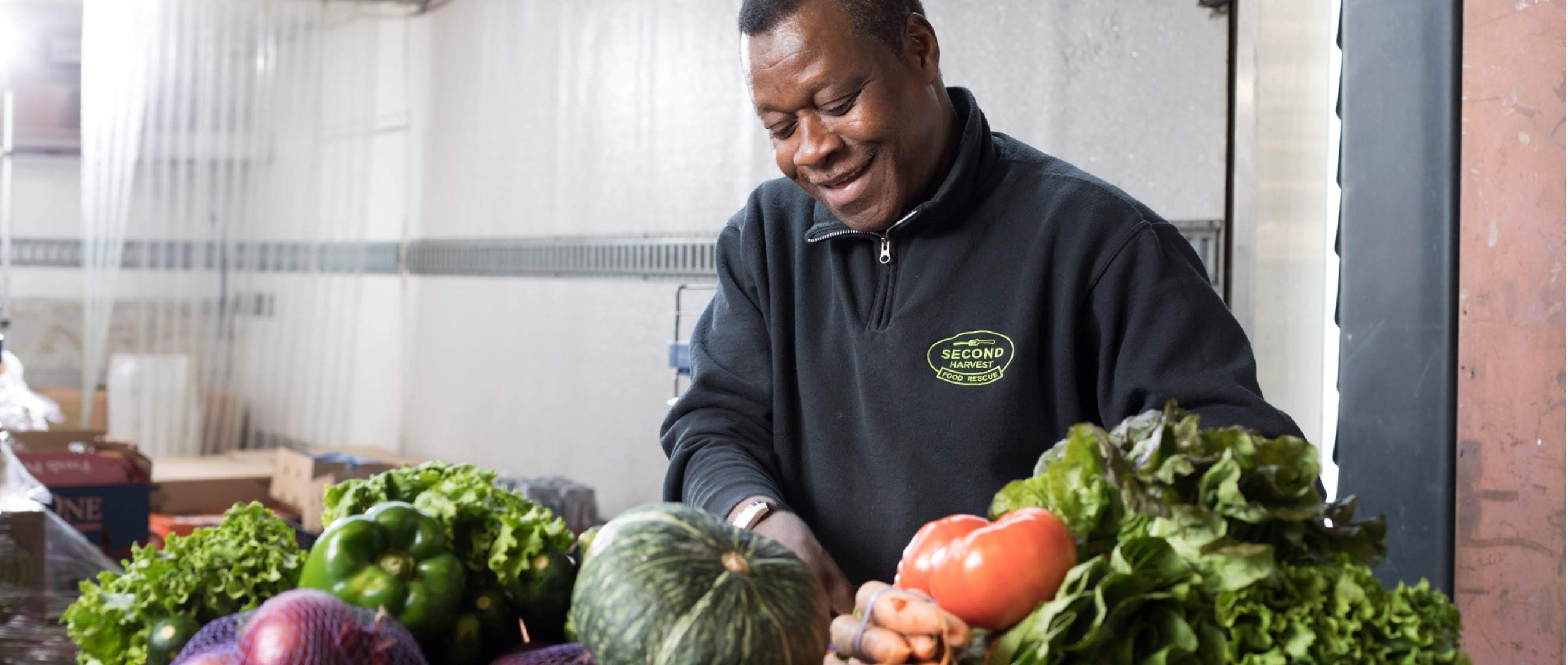 Man smiling, working with fresh produce in a warehouse.
