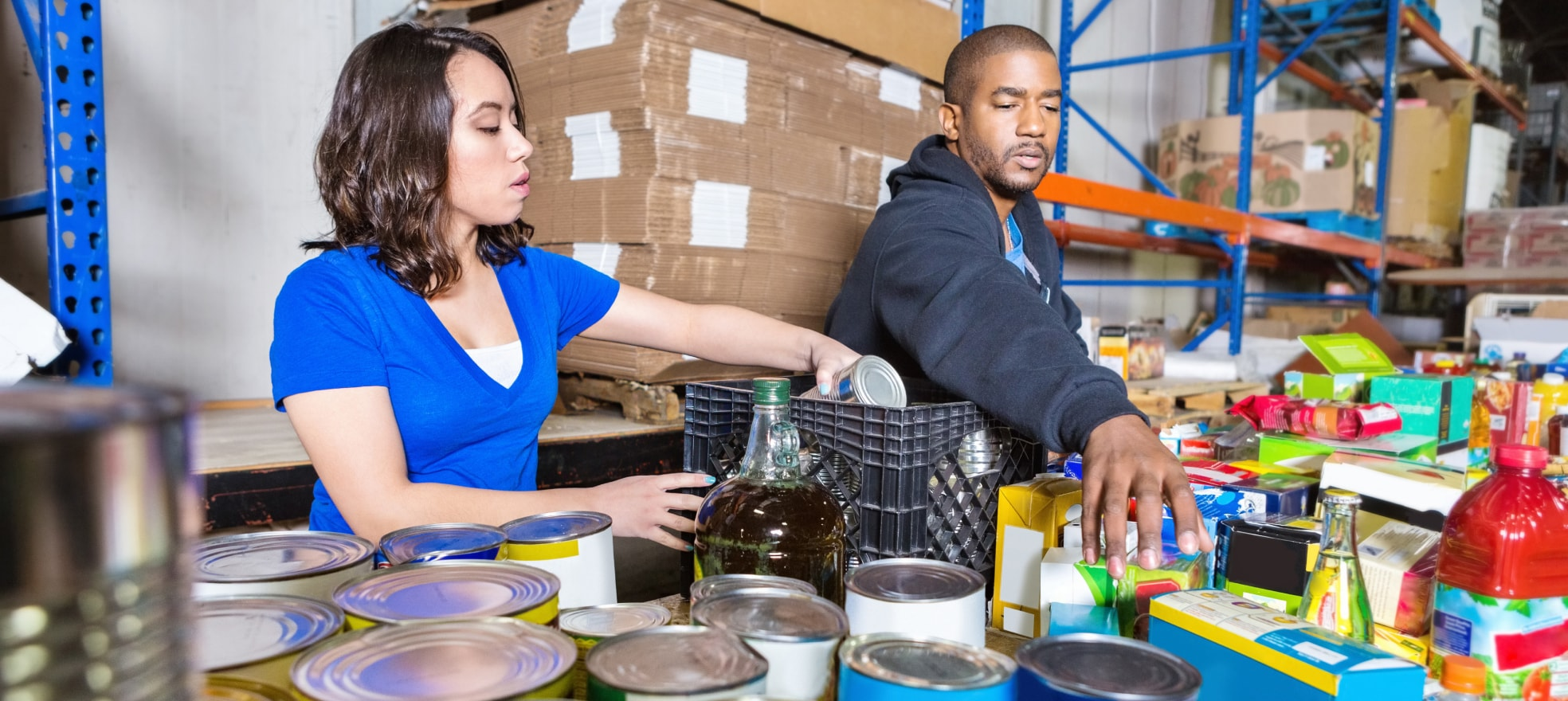 A woman and a man working together sorting cans of food in a warehouse.