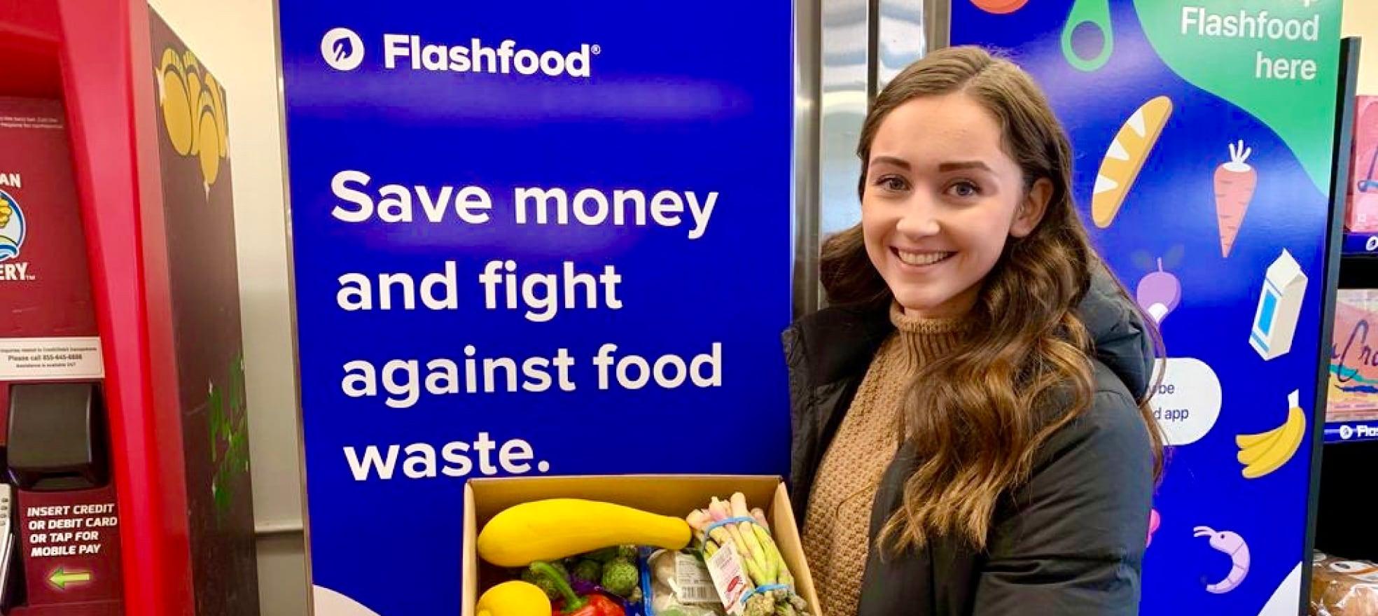 Jeune femme tenant une boîte de légumes frais devant une bannière Flashfood.