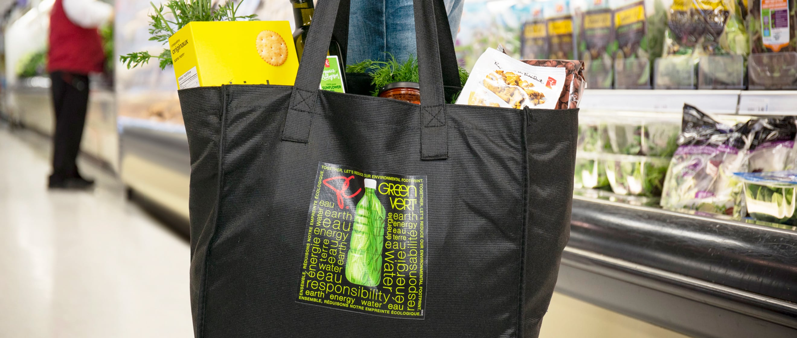 Shopper holding a reusable black bag back with groceries in it.