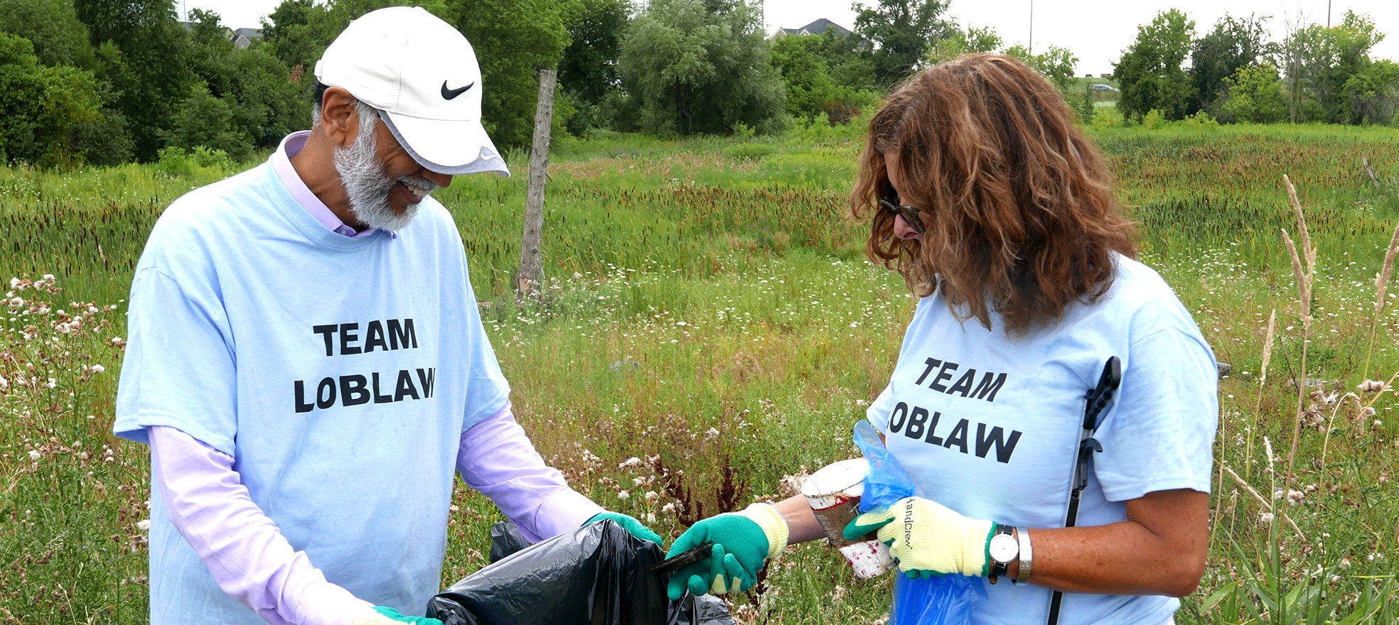 Two people in Team Loblaw T-shirts cleaning up trash in a field.