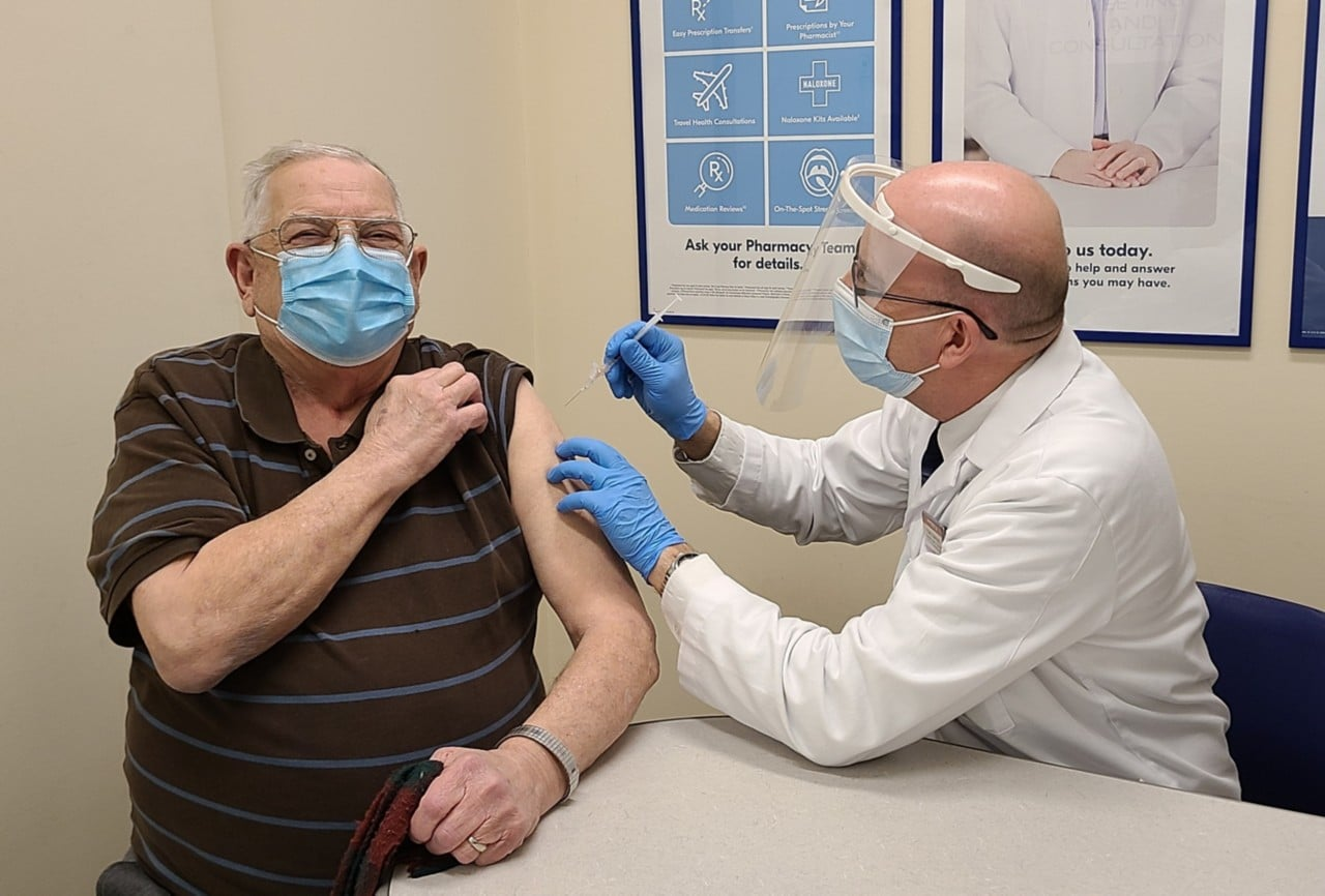 Shoppers Drug Mart Associate Owner Tony Alm gives the store's first COVID-19 vaccine to Eugene Bochon in Edmonton, AB