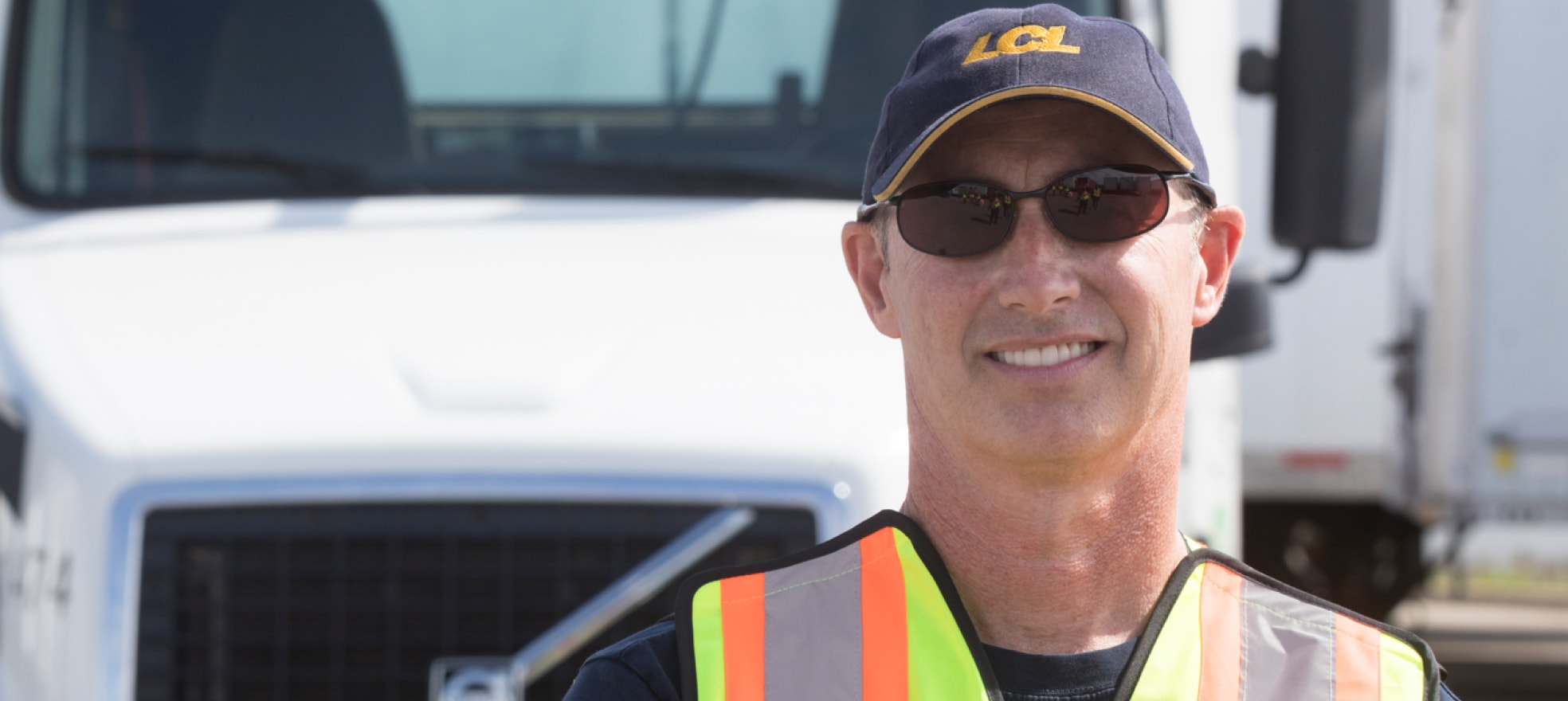 Man in safety vest smiling in front of a truck.