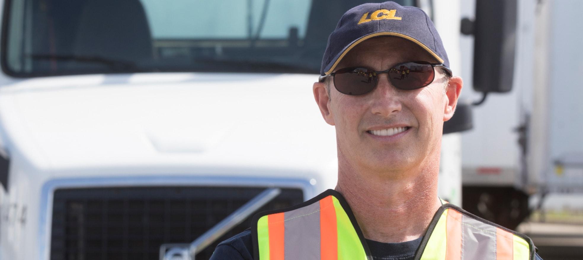 Homme portant une veste de sécurité souriant devant un camion.