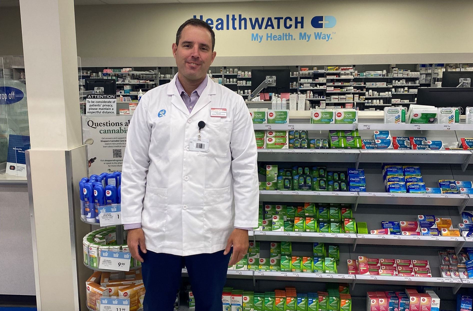Bryce stands in front of the pharmacy counter at Shoppers Drug Mart smiling