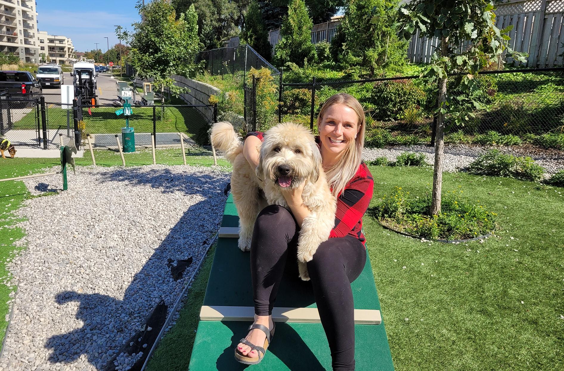 Caylyn s'assoit à l'extérieur sur une table avec son chien sur les genoux.