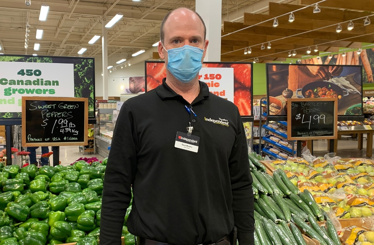 Man standing in grocery store produce department