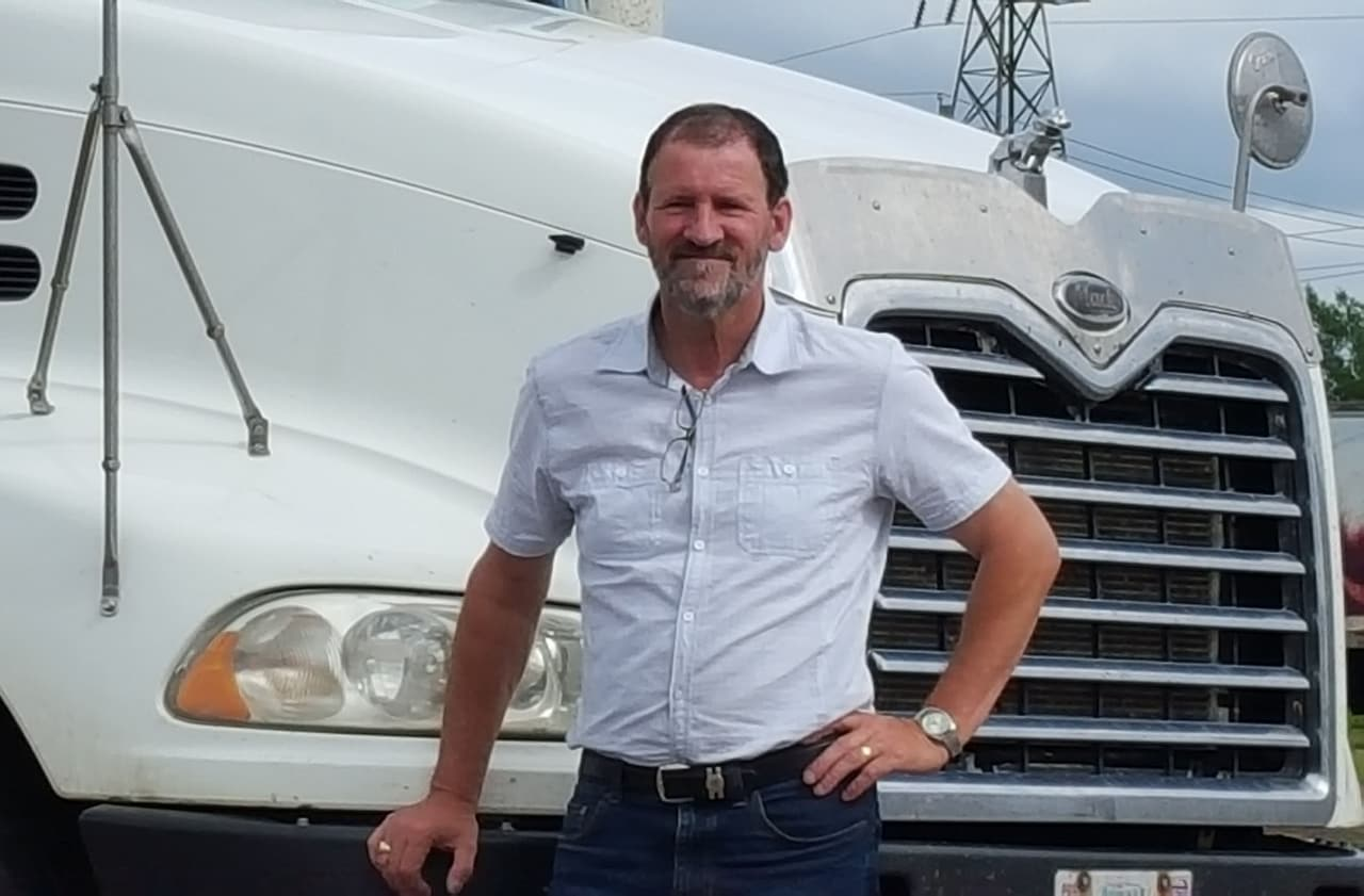 Edgar stands in front of a truck smiling