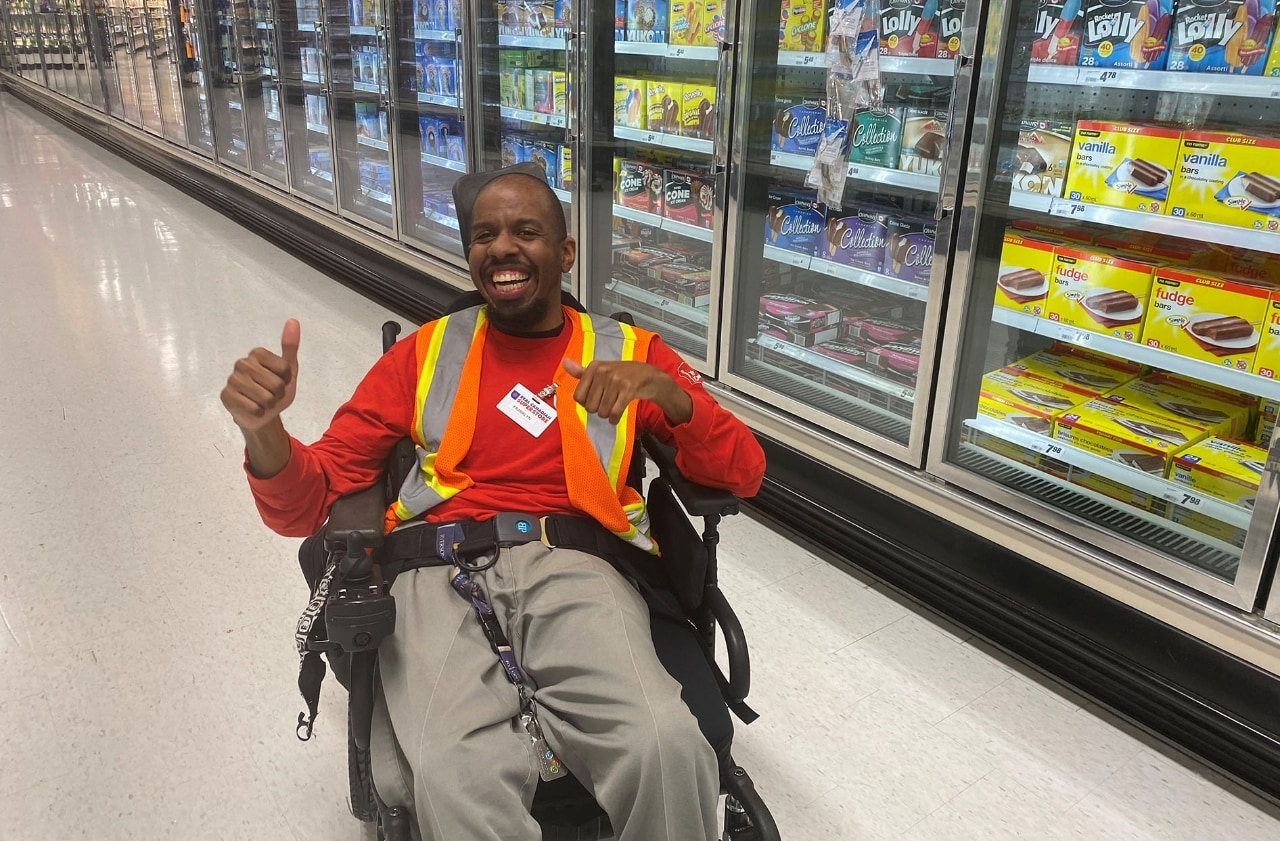 A man with cerebral palsy sits in his wheelchair in a grocery store aisle giving a thumbs up while smiling at the camera