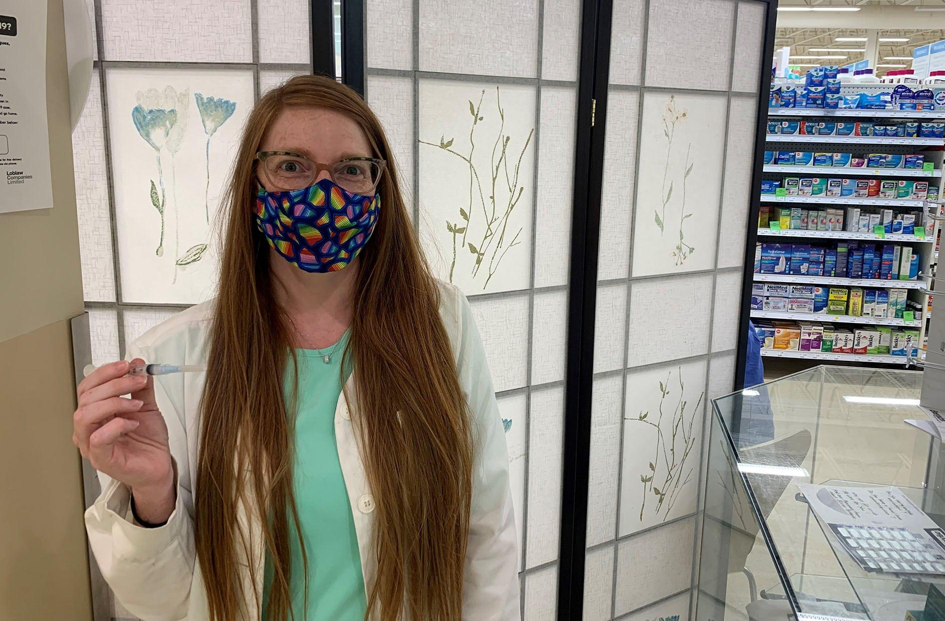 Jenna porte un masque facial tout en tenant une seringue utilisée pour les vaccins.