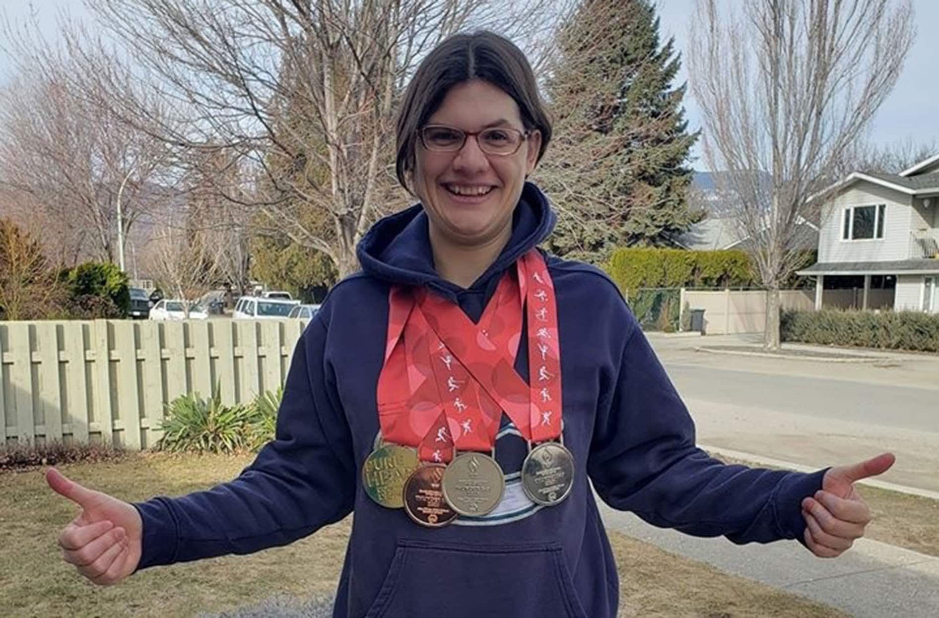 Kelsey stands outside with her thumbs up as she smiles with her medals around her neck