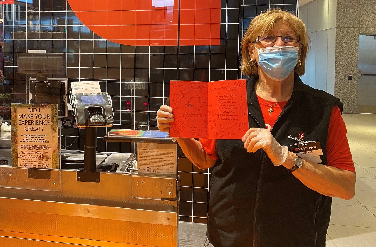 Woman wearing face mask, standing in grocery store, holding up signed greeting card