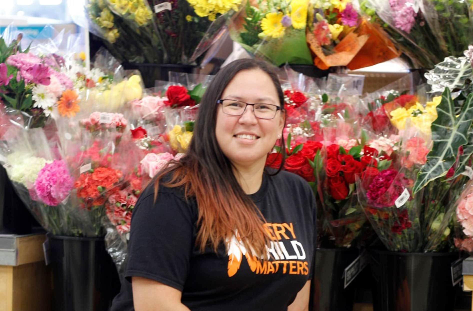 Nina est assise devant des arrangements floraux dans un magasin.