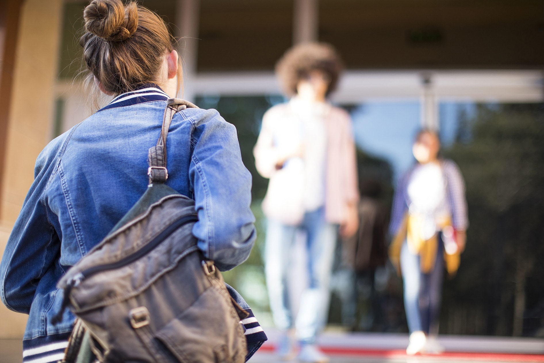 The back of a young girl walking forward carrying a school bag