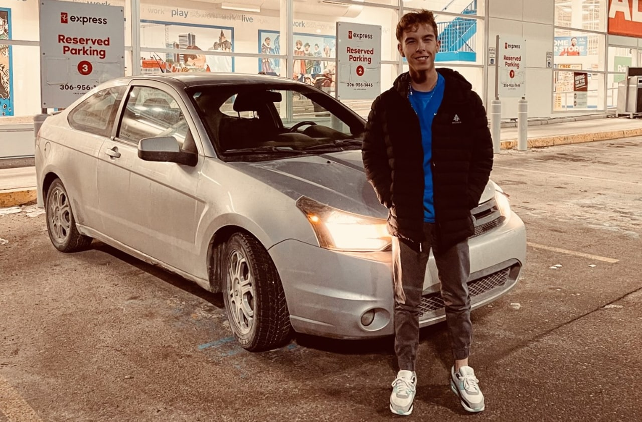 Teenage boy standing next to car in store parking lot