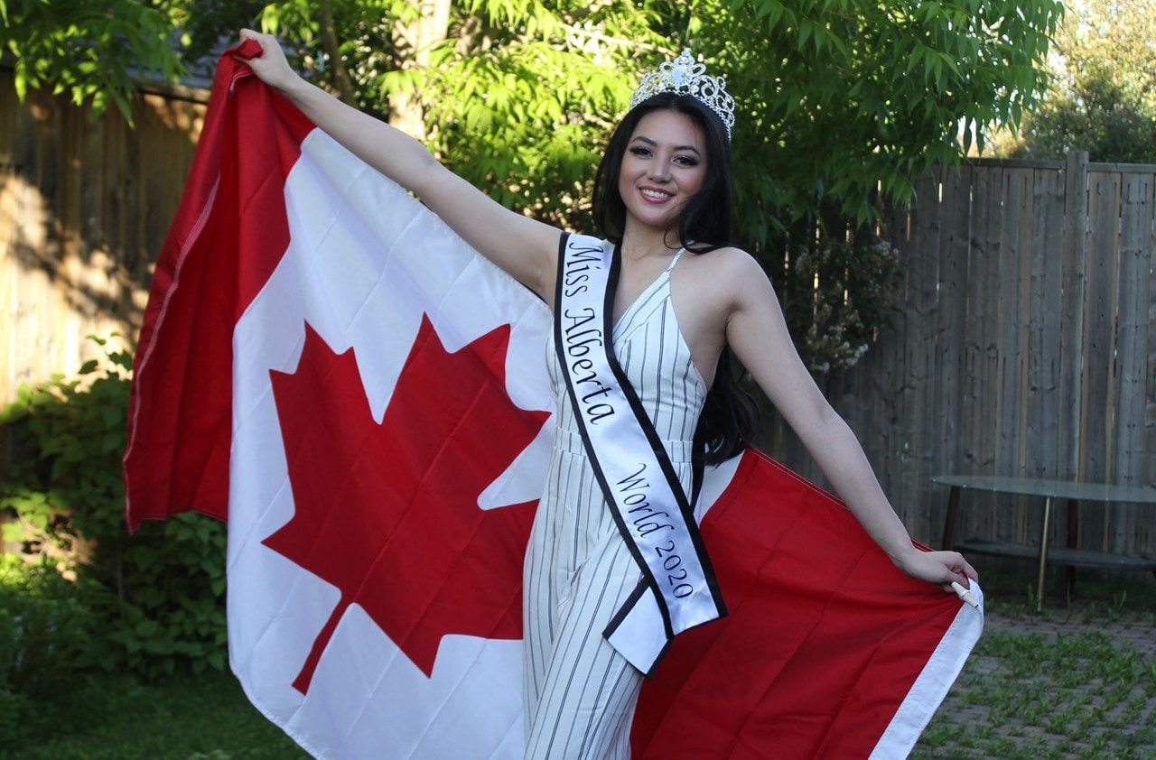 "Young woman with ""Miss Alberta World 2020"" sash on, holding flag of Canada behind her"
