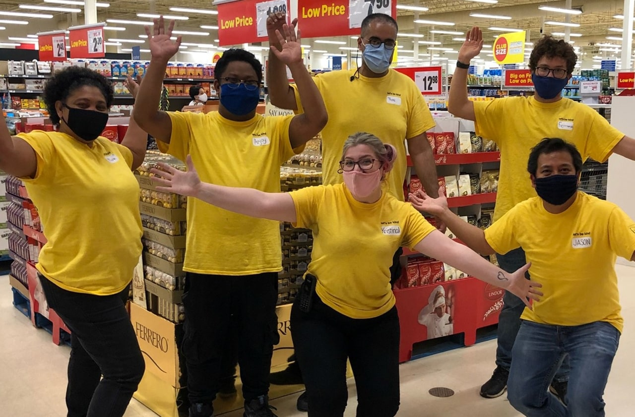 Six colleagues in yellow shirts with their arms up