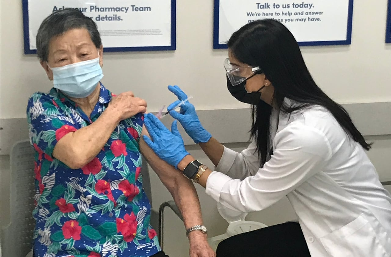 Pharmacist administering vaccine to older person