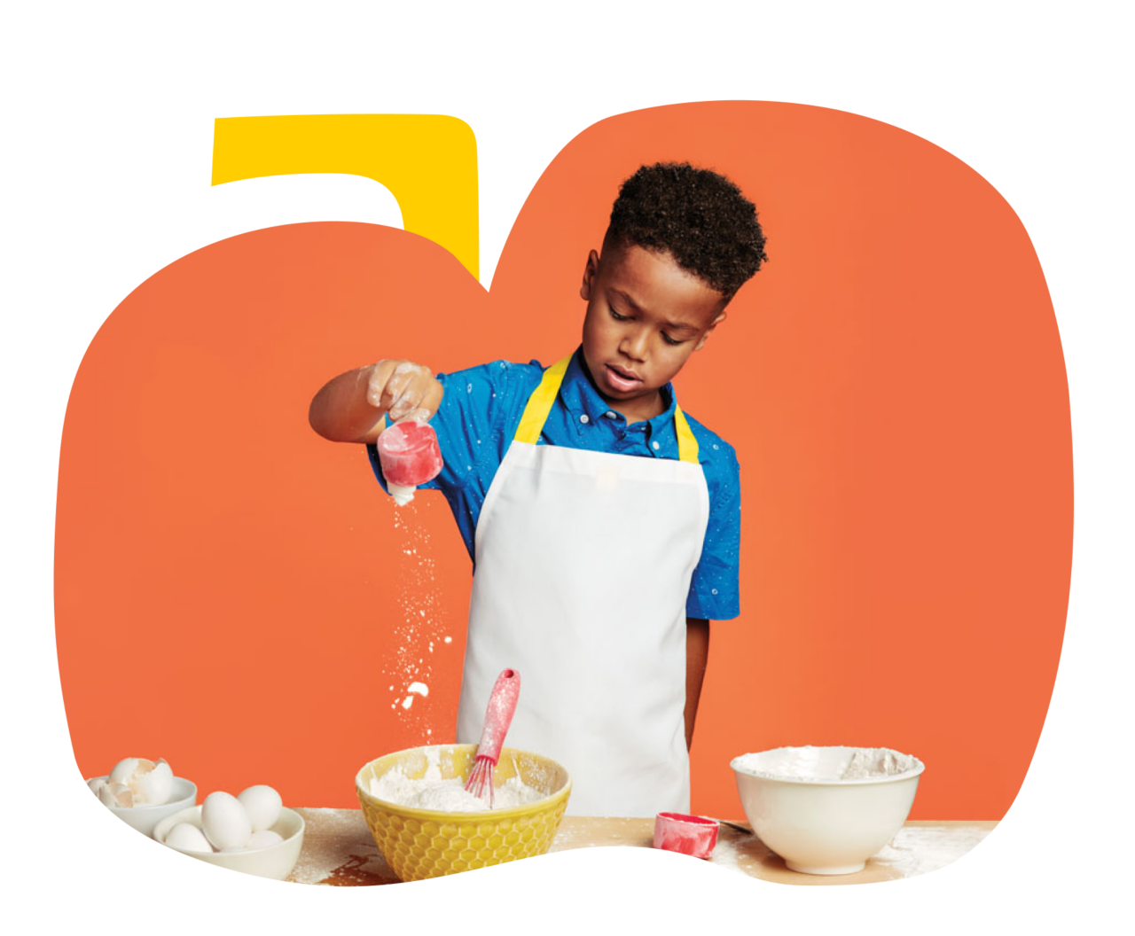 Young boy pouring a cup of flour into a mixing bowl.